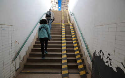Technical Penguins Web Accessibility Guide: An image of a tall staircase covering at least two floors is visible in a public space. The backs of two people ascending the stairs are visible at left. No elevator or other automated technology is visible; instead, two thin tracks are laid over the right side of the staircase, about as far apart as the wheels on a wheelchair, making a very steep ramp.