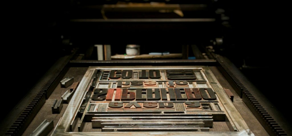 Technical Penguins Guide to the WordPress Gutenberg Editor: A photo of a printing plate, with letters typeset, sitting on a press.