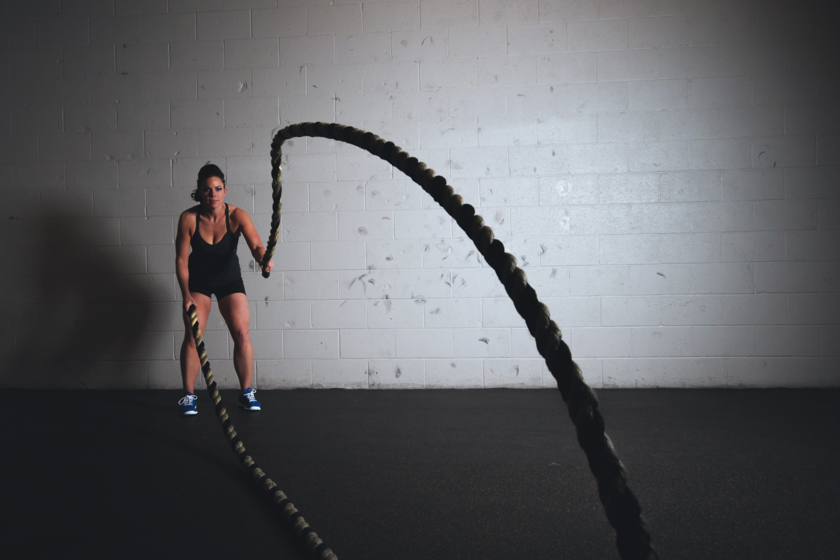 Technical Penguins White Paper on WordPress speed optimization: A background image shows a woman in athletic wear using ropes as part of a Crossfit workout.